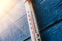 Thermometer on the old wooden wall, concept of hot weather. Stock Photo