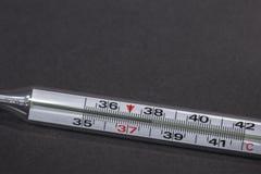 Thermometer op witte achtergrond ter beschikking wordt geïsoleerd die Temperatuur die door een thermometer meten Koorts het meten Royalty-vrije Stock Afbeelding