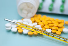 Thermometer and pills Stock Photography