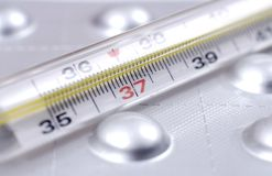 Thermometer and pills Stock Image