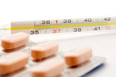Thermometer and pills. Picture closeup Royalty Free Stock Images