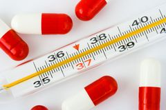 Thermometer and pills Royalty Free Stock Images