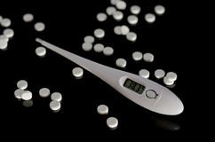 Thermometer and pills. On a black background stock photography