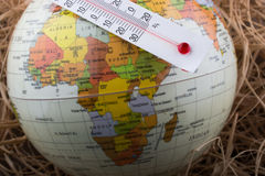 Thermometer placed on a little globe Royalty Free Stock Photos