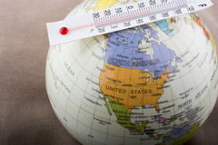 Thermometer placed on a little model globe Royalty Free Stock Photo