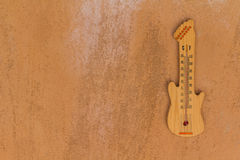 Thermometer shaped guitar. On cement wall background Stock Image