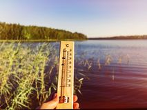 Thermometer showing 30 degrees Celsius of heat against the background of the lake water and the blue sky in sunlight.  stock photo