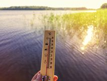 Thermometer showing 30 degrees Celsius of heat against the background of the lake water and the blue sky in sunlight.  royalty free stock photography