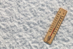 Thermometer in the snow with freezing temperatures stock photography