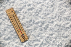 Thermometer in the snow with freezing temperatures royalty free stock image