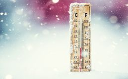 Thermometer on snow shows low temperatures in celsius or farenheit stock photos
