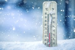 Thermometer on snow shows low temperatures - zero. Low temperatures in degrees Celsius and fahrenheit. Cold winter weather - zero