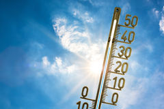 Thermometer in the summer sun. A thermometer under a blue, summer sky with clouds stock photography