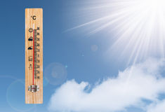 Thermometer and the sun on a blue sky Stock Photo