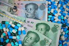 Thermometer,syringe and pills  on Yuan banknotes for health conc Stock Photos