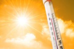 Thermometer tegen de achtergrond van een oranjegele hete gloed van wolken en zon, concept heet weer stock foto