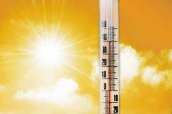 Thermometer tegen de achtergrond van een oranjegele hete gloed van wolken en zon, concept heet weer stock afbeelding