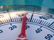 Thermometer tegen water stock afbeelding
