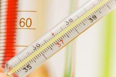 Thermometer- und Chemikaliengefäße am Hintergrund Stockfotos