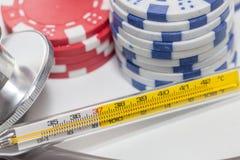 Thermometer und Stapel des Kasinos bricht auf Weiß ab Stockfoto