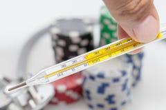 Thermometer und Stapel des Kasinos bricht auf Weiß ab stockfotografie