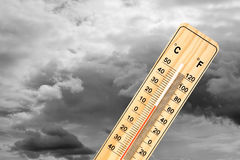 Thermometer under cloudy sky. Thermometer measuring an outside temperature of 15 degrees Celsius with cloudy sky in the background stock image