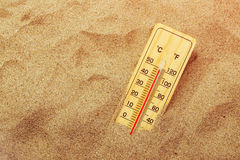 Thermometer on warm desert sand Royalty Free Stock Photo