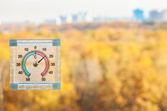 thermometer on window and blurred yellow city park royalty free stock image