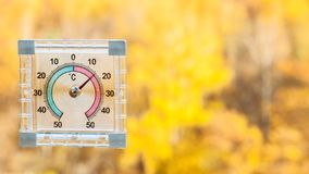 thermometer on window and blurred yellow forest royalty free stock images