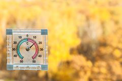 thermometer on window and blurred yellow trees stock photo