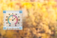thermometer on window and blurred yellow woods stock photos