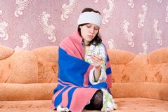 Thermometermädchen in einem Bademantel auf der Couch Lizenzfreie Stockfotos