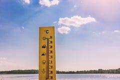 Thermometervertretung 30 Grad Celsius von der Hitze vor dem hintergrund des Seewassers und des blauen Himmels im Sonnenlicht stockbilder