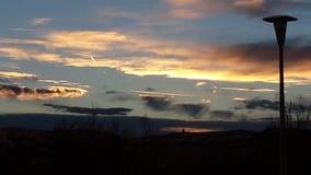 日落的另一时刻与反射在云彩的太阳的在Thermopolis, WY 库存照片
