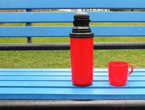 Thermos. Tea thermos at bench in park Stock Image