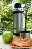 Thermos  and apple on background of the nature Stock Photo