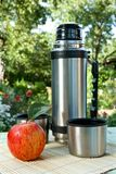 Thermos  on background of the nature Royalty Free Stock Photography