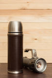 Thermos bottle with a flashlight on the table. royalty free stock photography