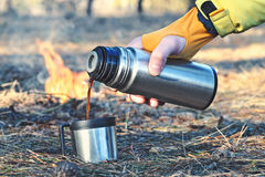 Thermos bottle outdoor near the campfire. Man pours in a cup or mug hot coffee, tea or mokka from a thermos bottle outdoor near the campfire in the forest Stock Images