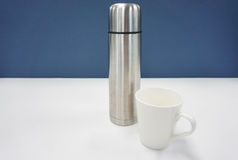 Thermos bottle with white mug Stock Images