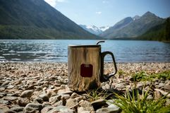 Thermos cup of coffee on wood with nature on background. Tourism and travel. Travel thermo mug with brewed tea amid the beautiful lakes and high mountains Stock Photography
