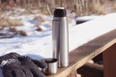 Thermos with cup and gloves in winter stock photography