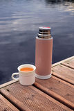 Thermos with cup on pier Royalty Free Stock Images