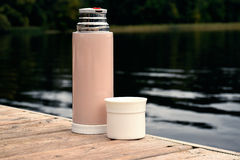 Thermos with cup on pier Royalty Free Stock Image