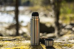 Thermos, cup and pinecone- picnic on mossy rock royalty free stock photography