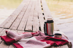 Thermos with a cup standing on a plaid on a wooden bridge near lake. Autumn mood Royalty Free Stock Images
