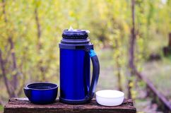 Thermos for drinks. Thermos with two mugs. With a thermos on the nature. Camping with a thermos. Fall. Thermos for drinks. Thermos with two mugs. With a thermos Royalty Free Stock Photo