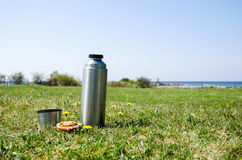 Thermos on grass field. Thermos with bread on a grass field at the coast in springtime Stock Photo