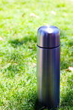 Thermos on the grass Stock Photography