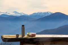Thermos with hot tea and sandwiches are on table outdoor on background of pictorial landscape with mountains royalty free stock images